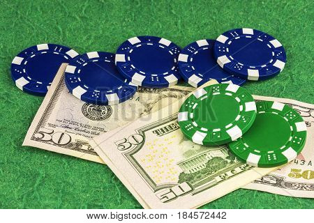 On the green cloth of the poker table are two bills of $ 50 green and blue chips