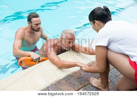 Lifeguards rescuing unconscious senior man from swimming pool