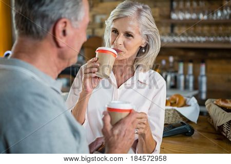 Senior couple interacting with each other while having coffee in café