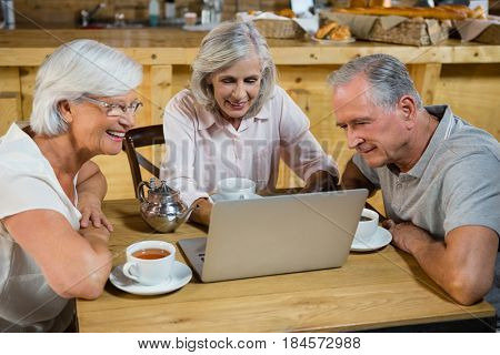 Group of senior friends using laptop in café