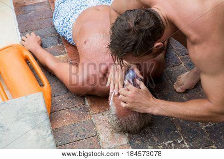 Lifeguard helping unconscious senior man at poolside