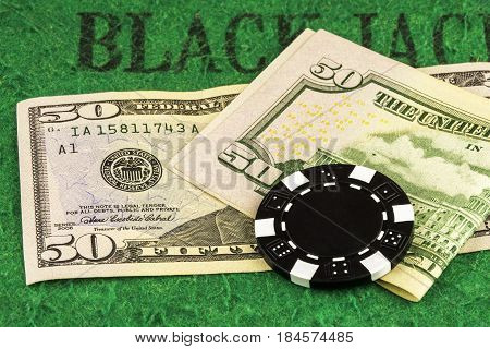 On the green cloth of the poker table there are two banknotes of 50 dollars and one black chip