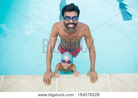 Portrait of father and son wearing swimming goggles in pool at leisure center