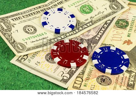 On the green cloth of the poker table is one five and ten dollar bills and white blue and red chips