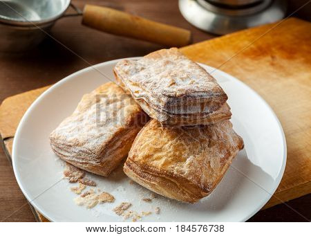 Puff Pastries Stacked In A White Plate On A Wooden Table