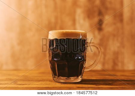 Dark craft beer in british dimpled glass pint mug on bar table