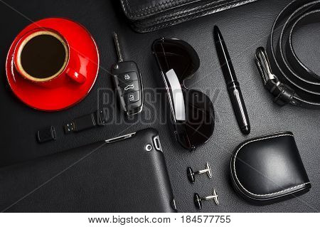 Man accessories in business style with cup of coffee, gadgets, car key, cufflinks, eyewear, briefcase and other luxury businessman attributes on leather black background, fashion industry, selective focus