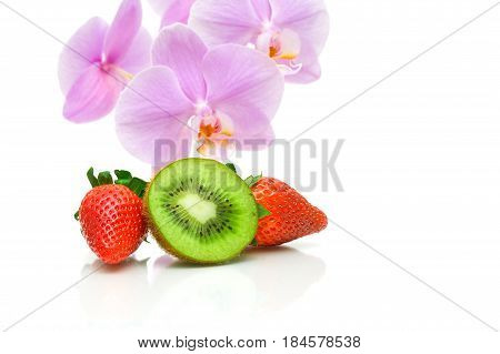 juicy kiw strawberries and orchid flowers on a white background. horizontal photo.