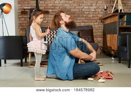 Little girl playing with father at home, combing his hair.