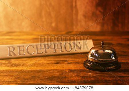 Reception bell at hotel check in desk warm retro tone selective focus