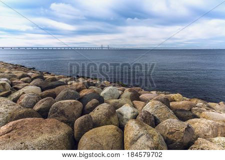 Large rocks on the sea shore seascape and Oresund bridge in the background on cold winter day with dramatic sky