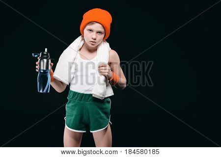 Confident Sporty Boy With Towel On Neck Holding Sports Bottle With Water Isolated On Black