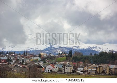 small houses, hotels, in the Georgian town of Bakuriani, a massive snowy mountains in the gloomy clouds