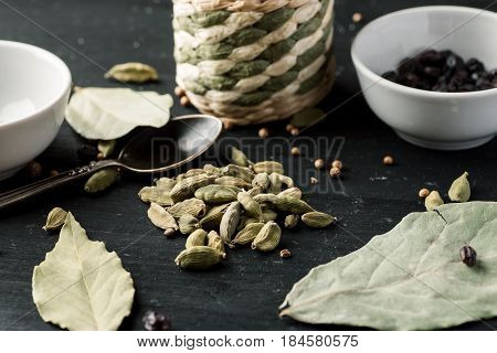 Pile Of Cardamon Seeds Among Other Condiments And Kitchen Stuff On A Black Wooden Table