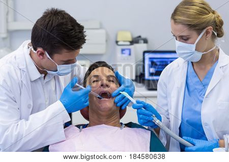 Dentists giving anesthesia to male patient in clinic poster