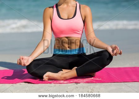 Low section of woman meditating in lotus position at beach
