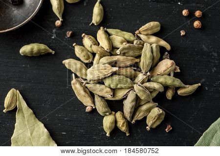 Pile Of Dry Cardamon Seeds On A Black Wooden Table, Top View