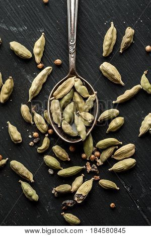 Cardamon Dry Seeds With Metal Spoon On A Black Wooden Table Top View, Flat Lay Composition