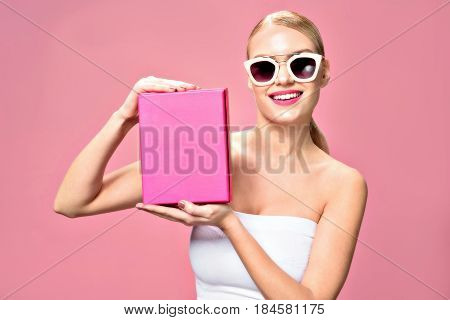 What could it be. Waist up portrait of happy blonde girl with sunglasses presenting box by her hands, isolated on pink background