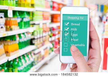 Hand holding smart phone with grocery shopping check list application on screen background business and technology concept