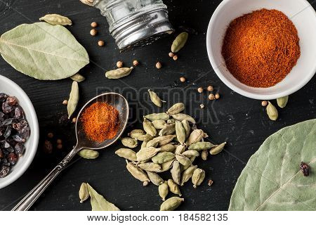 Ground Paprika, Cardamon Seeds And Other Condiments On A Black Wooden Table, Top View, Flat Lay Comp