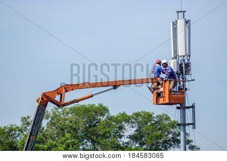 Kota Kinabalu,Sabah-June 18,2016:Technicians maintenance on telecommunication tower doing ordinary maintenance & control to an antenna for communication in Kota Kinabalu,Sabah,Borneo,Malaysia.