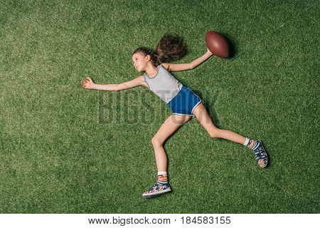 Top View Of Little Sportive Girl Throwing Rugby Ball On Grass, Athletics Children Concept