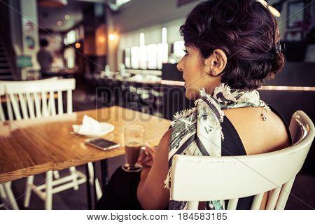 Woman sitting in coffee shop restaurant