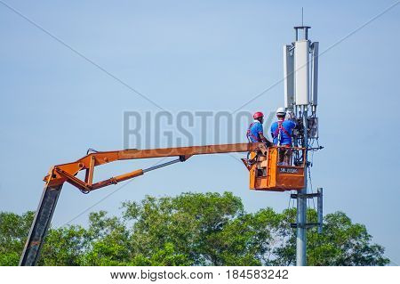 Kota Kinabalu,Sabah-June 18,2016:Technicians maintenance on telecommunication tower doing ordinary maintenance & control to an antenna for communication in Kota Kinabalu,Sabah,Borneo,Malaysia.