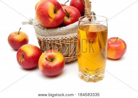 Ripe apples and a glass with apple juice on a white background. Horizontal photo.