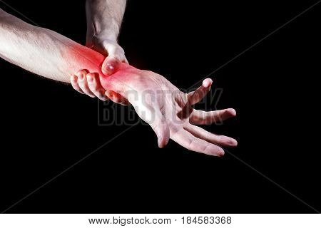 A man a woman holding her painful wrist experiencing pain a tunnel syndrome red spot on the black background
