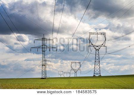 Pylons on green field under cloudy sky - high-voltage network - spring landscape. Czech Republic Europe.