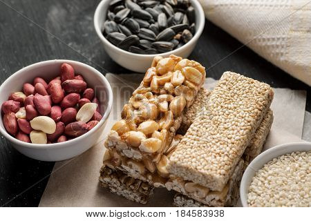 Peanut And Sesame Brittle Stacked On A Piece Of Paper With Ceramic Bowls With Same Ingredients