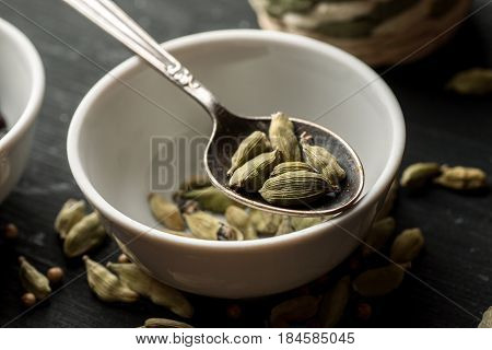 White Ceramic Bowl With Cardamon Seeds In It And Metal Spoon Above On A Black Wooden Table