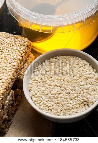Sesame Seeds In A White Ceramic Bowl And Few Brittle With Honey Jar, Closeup Shot, Vertical
