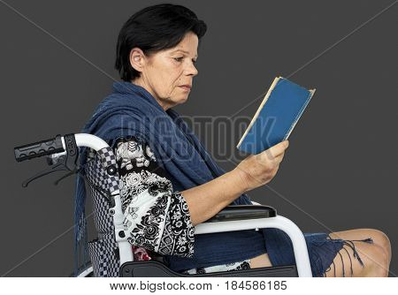 Disable Adult Woman Reading Book on Wheelchair Studio Portrait