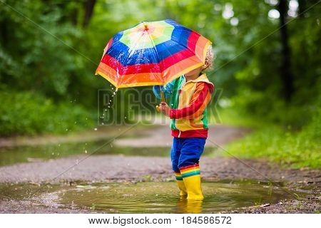 Child Playing In The Rain Under Umbrella