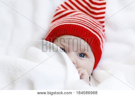 Cute adorable baby child with Christmas winter cap on white background. Happy baby girl or boy smiling and looking at the camera. Close-up for xmas holiday and family concept.