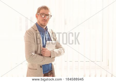 Young Businessman With Glasses Working On Tablet Computer Outside Office