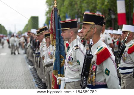 Paris. France. July 14 2012. Rows of foreign legionaries of the French foreign legion with a banner during the parade on the Champs Elysees in Paris.