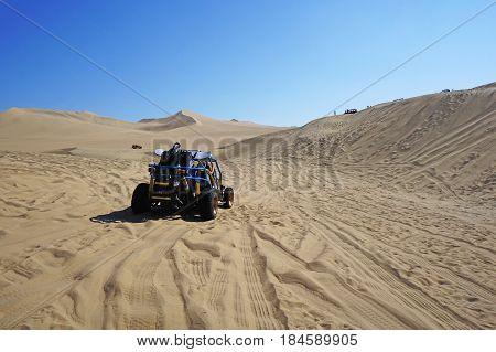 A dune buggy taking a ride through mountains of sand in Huacachina, Peru