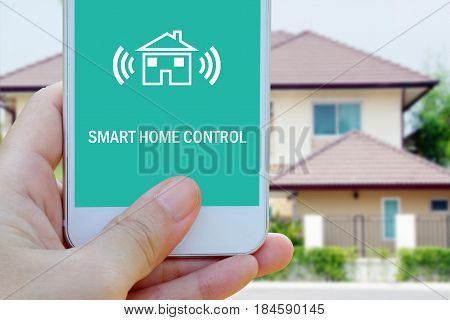 Hand using smart phone with smart home control device on screen over blurred house background smart home concept