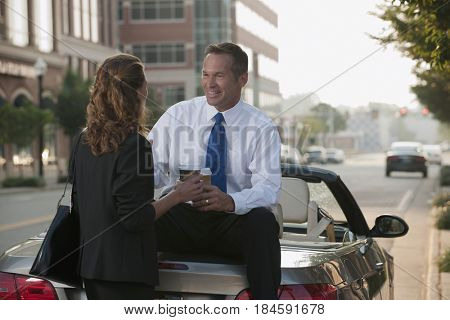 Caucasian businessman sitting on car talking to co-worker