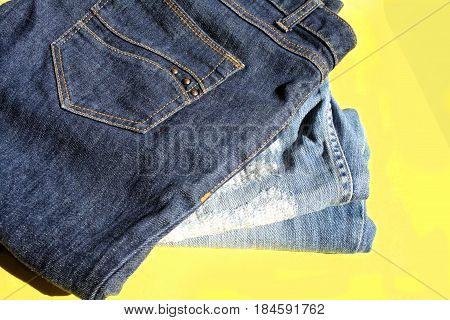 jeans laid in a pile on a yellow background