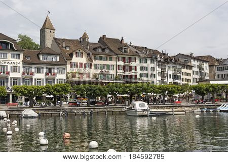 Rapperswil Switzerland - May 10 2016: Boats are moored at the marina on the shore of the Lake Zurich. There are trees that grow along the promenade and historical townhouses can be seen in distance