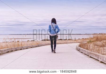 A Chinese woman walking on a boardwalk between Silver Sands State Park and Walnut Beach in Milford Connecticut on an overcast day.