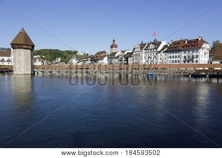 Lucerne Switzerland - May 05 2016: Landmarks by the river Reuss. The Chapel Bridge connects the two banks of the river and in the distance the townhouses along the waterfront can be seen
