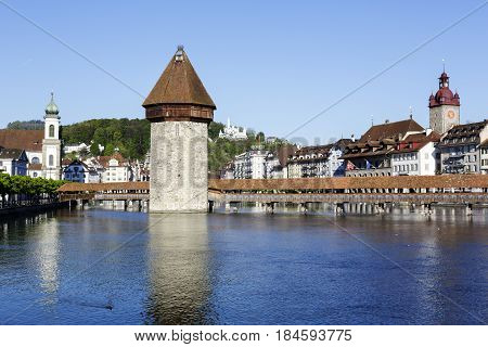 Lucerne Switzerland - May 05 2016: A variety of well-known landmarks in the city such as a Roofed Chapel Bridge together with Octagonal tower are located by the River Reuss
