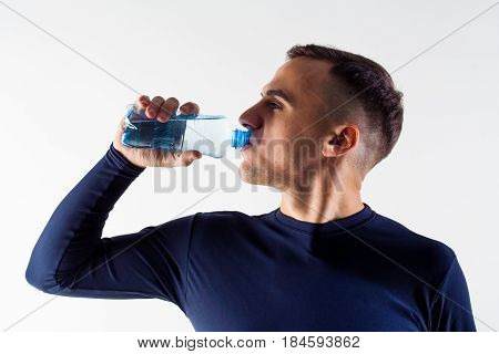 A man with a bottle of water. Sportsman with a bottle of water. Side view.
