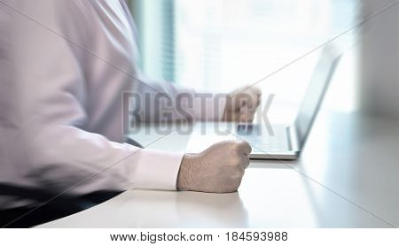 Angry businessman hit fist to table in office workstation. Very aggressive and mad entrepreneur or worker showing his frustration. Crisis, failure and problem with business. Anger management concept.